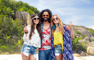 happy hippie friends showing peace on island beach