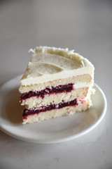 Slice of layered sponge cake with white frosting and jam filling