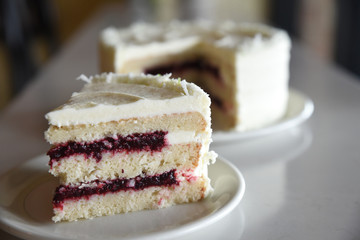Layered sponge cake with white frosting and jam filling