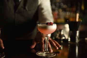 Serving a pink colour cocktail with fruit garnish