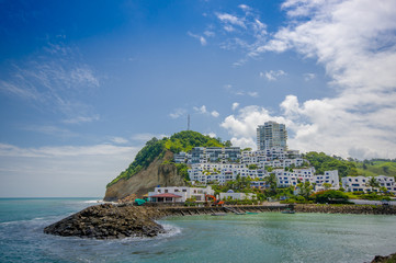 Beautiful rocky beach with a buildings structure of hotels behind in a beautiful day in with sunny weather in a blue sky in Same, Ecuador