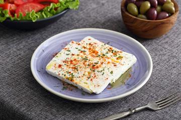 formaggio bianco con spezie pomodori e olive su tavolo grigio