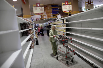 People buy food and other staple goods inside a supermarket in Caracas
