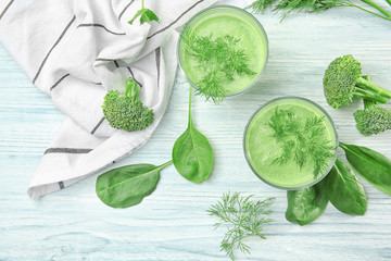 Glasses of fresh vegetable juice on wooden background