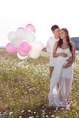 Portrait of a family in the chamomile field. Pregnant woman holds beads. Family with balloons.