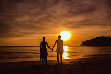 A couple holding hands during an amazing sunset. Loving couple in the pond at sunset hug