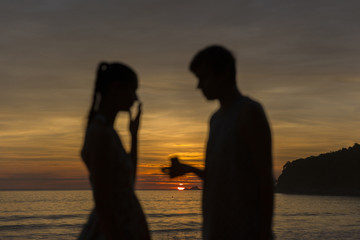Out of focus silhouette man propose marriage to a silhouette woman with sunrise background