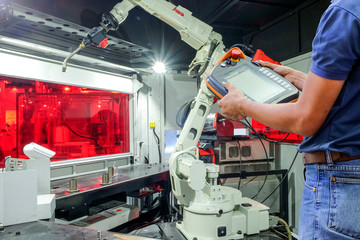 Engineers use a wireless remote control of robotic welding for smart factory, industry 4.0 concept