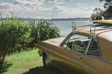 Vintage car with surfboard parked at the ocean