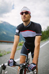 Portrait of a cyclist with his bike in the mountains