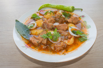 Tasty winter stew with meat and vegetables in bowl with ingredients over wooden table