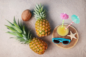 Sunglasses with glass of juice and pineapples on the beach sand