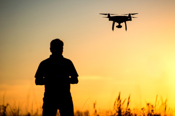 Young man operating of flying drone the setting sun Wall mural