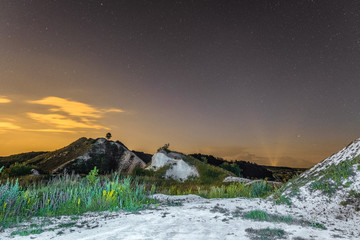 Starry night sky over the white chalky mountains. Natural landscape. Night view of the chalk hills. Archaeological monument - Krapivinskaya settlement, Belgorod region, Russia.
