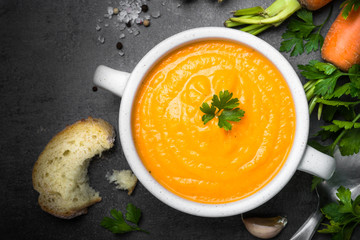 Carrot cream-soup on black table.