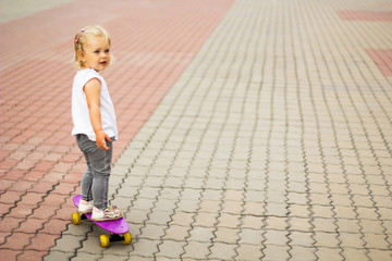 A blonde little girl is riding on a skateboard while standing. Space for text.