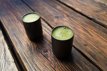 2 cups of matcha green tea on a wooden table macro close-up