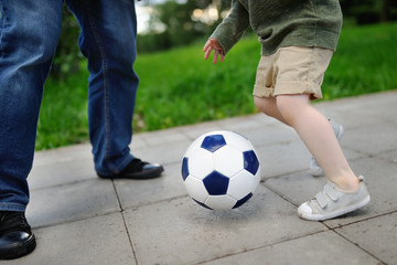 Little boy with his father having fun playing a soccer game on sunny summer day