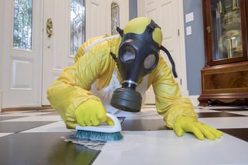 Mature woman in Haz Mat suit scrubbing floor with brush