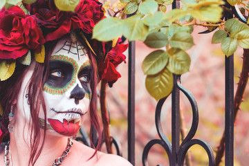 Close up portrait beautiful girl in makeup traditional Mexican Calavera sugar skull on the background of an iron fence with spikes. Day of the dead. Halloween celebration.