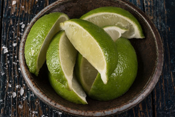 Lime wedges in pottery bowl