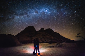 Landscape with Milky Way. Night sky with stars and silhouette of a couple.
