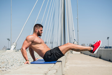 Young man doing workout for abdominal muscles