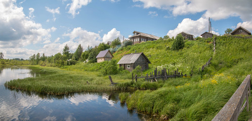 North Russian village. Summer day, river, old cottages on coast.