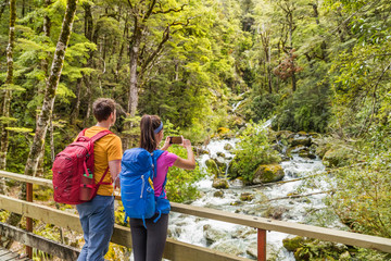 New zealand travel tourists taking phone picture on tramping hike in forest with backpacks. Woman holding smartphone taking photos of river on Routeburn track hikingtrail on South Island.