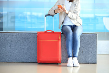 Red suitcase near sitting girl