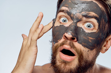 A man with a beard on a white isolated background apply clay cosmetic face mask