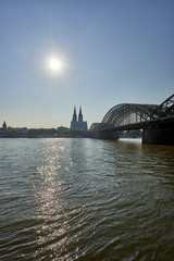 Cologne Cathedral in view past Hohenzollern Bridge as seen from Kennedy Ufer/ riverbank