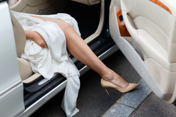 Girl in elegant white dress comes out of a luxury convertible car. The girl in beige expensive shoes feet have pegs sports car with the door open.