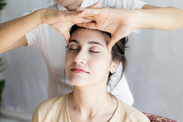 Beautiful young woman having head massage in spa salon. Woman with thai massage. Woman with relax emotion.