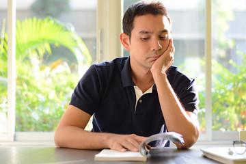 A man reading book - bored & moody concept