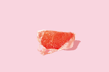 Peeled grapefruit on pink background, studio shot