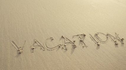 VACATION written on the beach sand washed aways by waves.