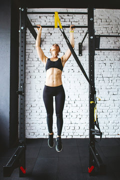 Young fitness woman doing pull ups in gym