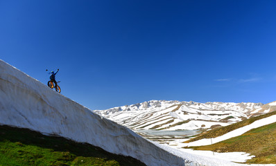 Adventure in high and snowy mountains with bike