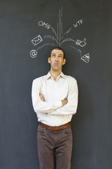 Single white adult man standing in front of a blackboard with drawn social media icons symbolizing frustration, stress and overload from modern communication
