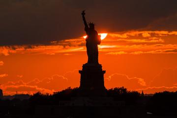 絶景、New York の日没 / New York のシンボル自由の女神の後ろに夕日が沈みます。雲間からの夕日と女神像が重なり、シルエットとなって 浮き上がります。