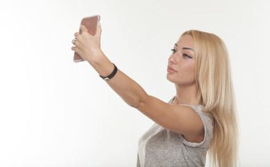 Young beautiful lady taking a selfie self portrait of herself smiling at he camera. Close up portrait of a attractive woman holding a smartphone digital camera.