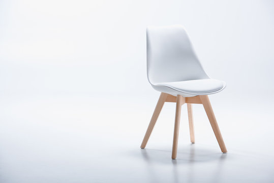 Studio shot of stylish chair with white top and light wooden legs standing on white