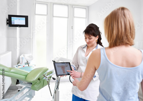 Female gynecologist showing uterus picture on a digital