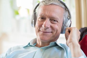 Senior Man Listening To Music On Wireless Headphones
