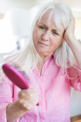 Senior Woman With Brush Corncerned About Hair Loss