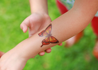 Butterfly Sticker on child hand, Dress up tattoos.