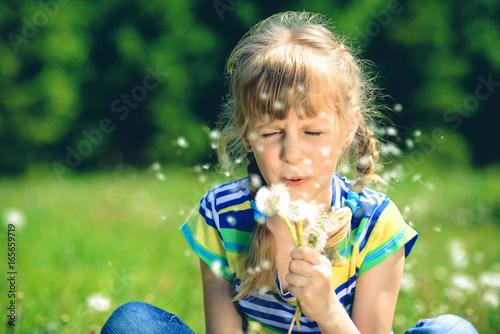 girl blows on dandelions