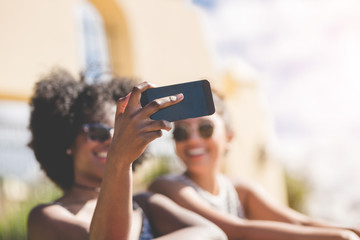 Young woman holding smartphone taking selfie with friend