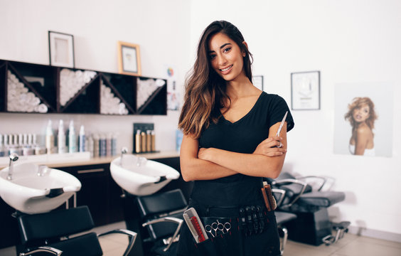 Female hairdresser standing in salon